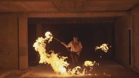 执行火展示的雍男性艺术家通过火焰喷射器在黑暗在慢动作 股票录像