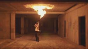 执行火展示的雍男性艺术家通过火焰喷射器在黑暗在慢动作 影视素材