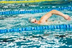 执行爬泳自由式冲程的游泳者在室内游泳池 图库摄影