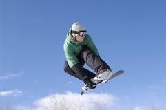 执行特技的挡雪板反对蓝天 免版税图库摄影
