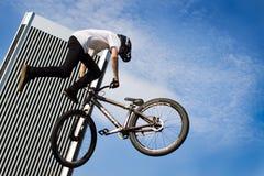 执行特技的自由式骑自行车的人在空中 免版税库存图片