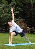 执行瑜伽在公园-延长的侧角姿势 免版税库存图片