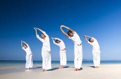 执行瑜伽海滩风景概念的人们 免版税库存照片