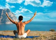 执行瑜伽的人在海运和山 免版税库存照片