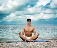 执行瑜伽的人在海运附近 免版税库存图片
