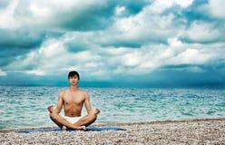 执行瑜伽的人在海运附近 库存图片