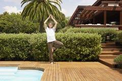 执行瑜伽的人由游泳池 免版税库存照片