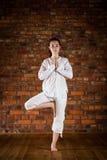 执行瑜伽的女孩对砖墙 免版税库存图片