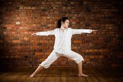执行瑜伽的女孩对砖墙 库存照片