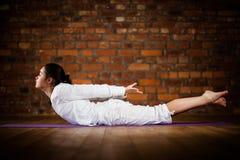 执行瑜伽的女孩对砖墙 免版税库存照片