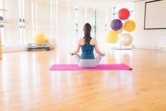 执行瑜伽的妇女在健身房 免版税库存图片