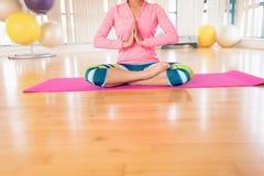 执行瑜伽的妇女在健身房 库存照片