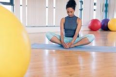 执行瑜伽的妇女在健身房 免版税库存照片