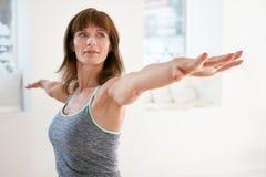 执行瑜伽的妇女在战士姿势 免版税库存照片