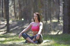 执行瑜伽的妇女在森林 库存图片