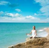 执行瑜伽的妇女在海运附近 图库摄影