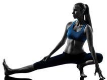 执行瑜伽的妇女舒展行程准备 免版税图库摄影