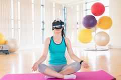 执行瑜伽的妇女,当使用虚拟现实耳机时 免版税库存图片