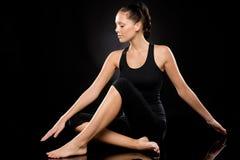 执行瑜伽的少妇与被舒展的胳膊 免版税库存图片