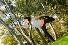 执行瑜伽的少妇在公园 免版税库存照片