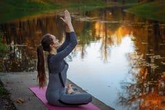 执行瑜伽的少妇在秋天城市公园执行 健康生活方式概念 免版税库存照片