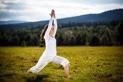 执行瑜伽的少妇室外 库存照片
