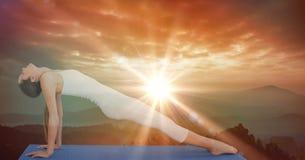 执行瑜伽的灵活的妇女侧视图在日落期间 图库摄影