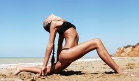 执行瑜伽的美丽的亭亭玉立的妇女在海滩 免版税库存照片