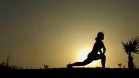 执行瑜伽的被集中的女孩剪影摆在,思考反对日落 库存图片