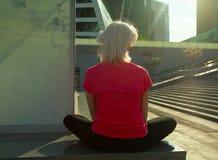 执行瑜伽的资深妇女 库存图片