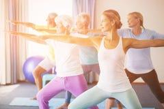 执行瑜伽的辅导员与前辈 免版税库存图片