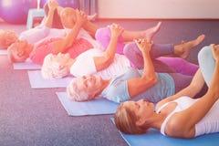 执行瑜伽的辅导员与前辈 免版税库存照片