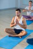执行瑜伽的年轻人 库存照片