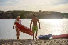 执行皮船的年轻愉快的夫妇对从水的沙子海滩在美丽的河或湖晚上 免版税库存图片