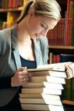 执行研究的妇女在图书馆里 免版税图库摄影