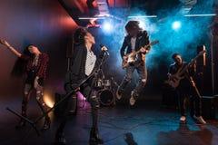 执行硬岩音乐的年轻不同种族的摇滚乐队 免版税库存照片