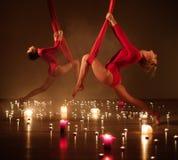 执行空中瑜伽的红色的两个女孩在松弛蜡烛点燃 免版税图库摄影