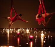 执行空中瑜伽的红色的两个女孩在松弛蜡烛点燃 库存图片
