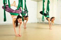 执行空中瑜伽锻炼的少妇 免版税库存图片