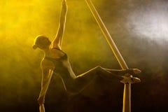 执行空中锻炼的优美的体操运动员 免版税库存照片