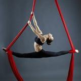 执行空中锻炼的优美的体操运动员 库存照片