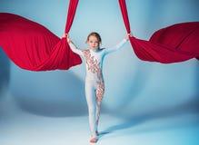 执行空中锻炼的优美的体操运动员 免版税库存图片