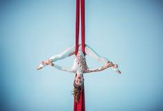 执行空中锻炼的优美的体操运动员 图库摄影