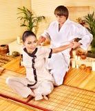 执行竹温泉的男性男按摩师按摩妇女。 免版税库存图片