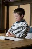 执行等级家庭作业的第1个男孩 免版税库存照片