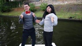 执行者在假肌肉填塞服装的人在浮动小船跳舞并且唱歌 股票视频