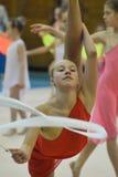 执行自由体操的美丽的少妇在体操竞争时 免版税库存照片
