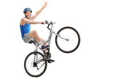 执行自行车前轮离地平衡特技的确信的年轻骑自行车的人 库存图片
