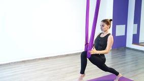 执行舒展妇女年轻人 健身,舒展,平衡、锻炼和健康生活方式 使用吊床的妇女 股票录像
