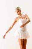 执行舞蹈移动的跳芭蕾舞者在工作室 免版税库存照片